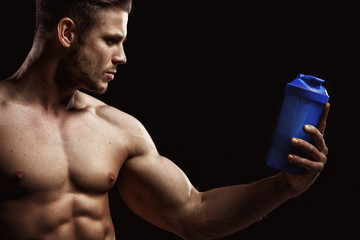 Model sports young man on dark background. Portrait of sporty strong muscle guy with protein drink in shaker. Sexy torso. Bodybuilding nutrition supplements, sport, workout, healthy lifestyle concep.