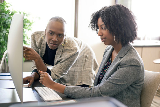 Black African American female co-workers having a business problem and annoyed or upset at each other.  The women lack teamwork or made a mistake at work.