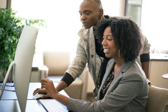 Black African American businesswomen or coworkers together in an office doing teamwork or job training.  The women are working together at a startup business.