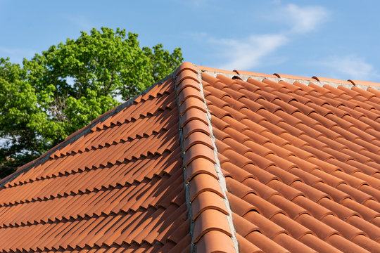 Orange roof tile pattern over blue and cloudy spring sky day and green tree in the background. The roof on modern house building. Close up