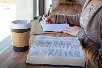 woman making notes while studying her bible