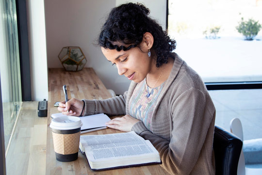 black woman studies her bible while drinking coffee and making notes