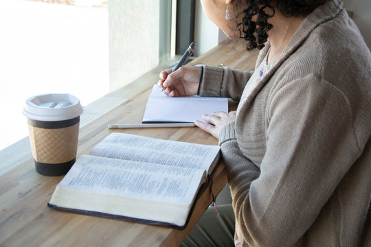 woman makes notes while she studies her bible