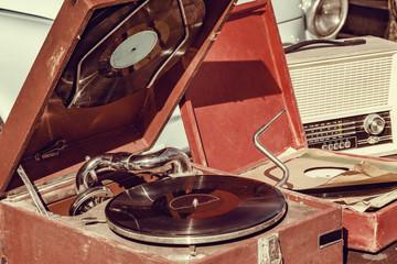 Vintage vinyl record player by the retro car.