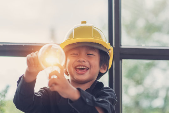 Funny Asian boys hold a light bulb that shines in their hands.