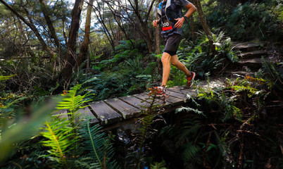 male running over a wooden bridge as part of an Ultra trail running event