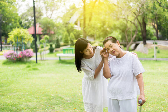 Elderly asian women having a faint suffering from migraine disease