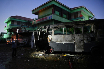 A man takes a photo of a bus that had been set on fire at the Brimon (Mobile Police) Dormitory Complex, Petamburan