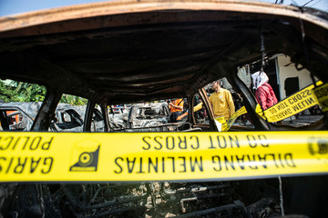 Investigators work at the scene of cars set on fire by protesters at Brimob (Mobile Police) Dormitory Complex, Petamburan, Jakarta
