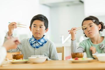 箸の持ち方を練習する兄と妹