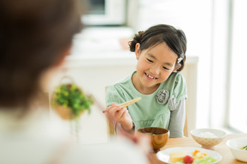 箸の持ち方を練習する女の子