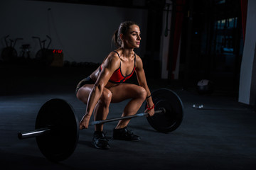 European muscular young fitness woman in khaki shorts doing heavy deadlift exercise in crossfit gym