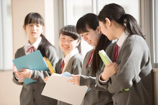 窓際で談笑をする女子学生