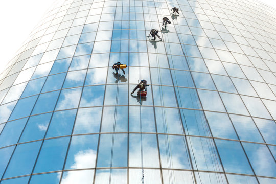 Five window washers work at a height on a high-rise building with a glazed facade against a blue sky with light clouds.