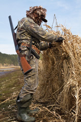 duck hunter makes a hunting blind of reeds
