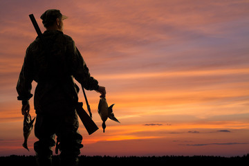 duck hunter with prey at sunset