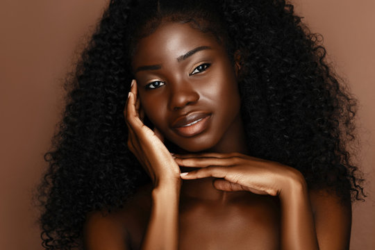 Beautiful skin care models with perfect dark skin and curly hair. African Beauty, spa treatment concept.