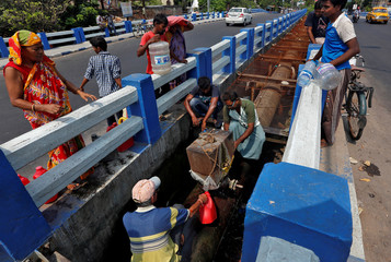 People fill their empty containers with water leaking from a broken pipe valve over a bridge in Kolkata