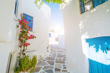 Street with beautiful pink bougainvillea flowers and white house walls. Colourful Greek street in...