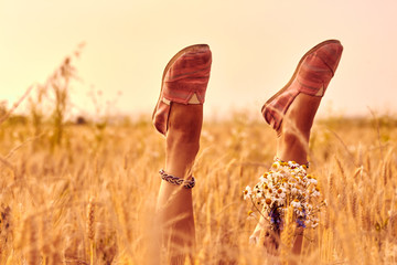 Girl holding flowers and lying in a wheat field.