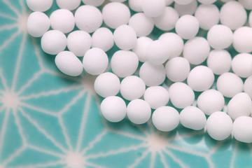 Globuli Kügelchen Detail auf blauen Hintergrun, Homöopathie Gesundheit