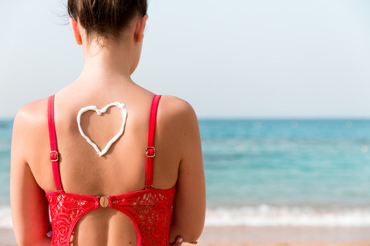 Beautiful girl in red swimsuit with sunscreen in shape of heart at the back at the beach