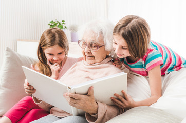 Grandmother with granddaughters looking white family photo album together Wall mural