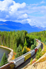 Wall Mural - Long freight train moving along Bow river in Canadian Rockies ,Banff National Park, Canadian Rockies,Canada.