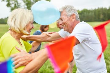 Senioren auf einer Party spielen mit Luftballons