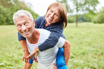 Senior Mann trägt seine Frau Huckepack