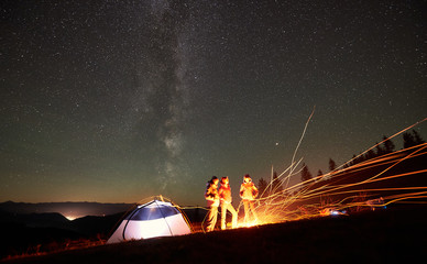 Night camping in the mountains. Happy friends backpackers having a rest together around campfire beside illuminated tourist tent. On background beautiful night starry sky full of stars and Milky way.