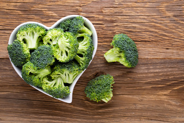 Fresh broccoli in a heart shaped bowl on a wooden background.