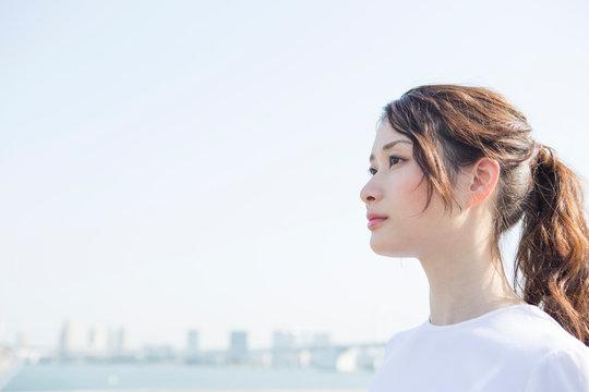 青空の下に立つ20代女性の横顔