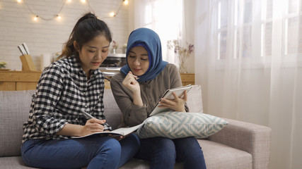Group of multi ethnic young students preparing for exams in home interior. two asian islam and chinese women college girls with pen writing notes sitting on sofa in dormitory. hard working teamwork. Wall mural