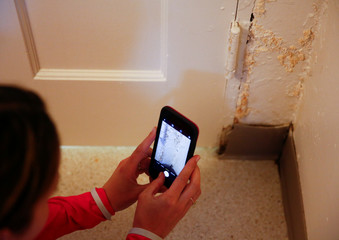 Tuttle takes a picture of pale orange mold behind the door of the guest bathroom in the basement of Lindholm's house at Joint Base Lewis-McChord