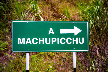 Big green pointing sign with stickers to Machupicchu on the forest background
