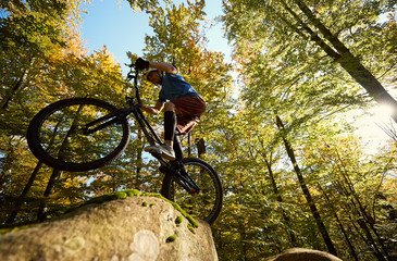 Professional sportsman cyclist riding on back wheel on trial bicycle, man biker making acrobatic stunt on the edge of big boulder in the forest on sunny day. Concept of extreme sport active lifestyle