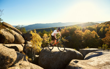 Active professional cyclist balancing on trial bicycle, male bicyclist making acrobatic stunt on top of big boulder in the evening, blue sky, forest and sunset on background. Concept of extreme sport