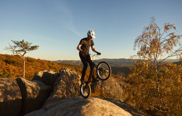 Young sportsman cyclist standing on back wheel on trial bike. Man biker making acrobatic stunt on the edge of big boulder on the top of mountain in the evening. Concept of extreme sport