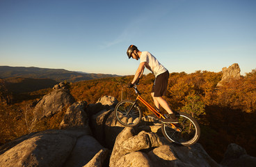 Athlete male cyclist balancing on trial bicycle on top of rocky mountain, rider making acrobatic trick on summer evening, blue sky and forest on background. Concept of extreme sport active lifestyle