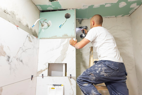 Plumber using electric screwdriver. Bathroom renovation concept. Marble ceramic tiles with spacers and grey cement walls in bathroom. Industrial builder working in toilet