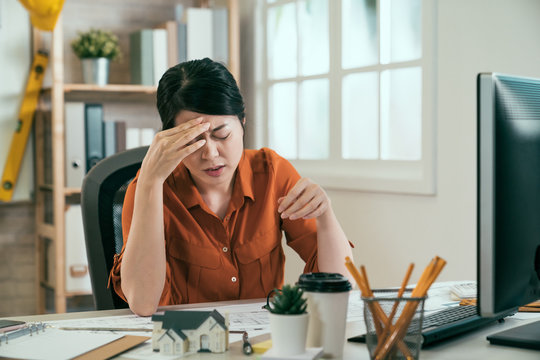 stressed chinese female architect having headache while working on blueprint in office. young asian girl designer sitting at desk using computer head painful. woman worker suffer migraines in studio.