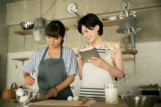 タブレットを確認しながらお菓子作りをする20代女性2人