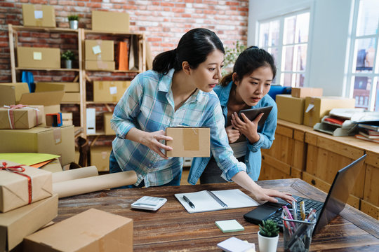 beautiful pretty female employees using laptop computer working in warehouse and browsing online shopping order document to confirm stock goods. young girls holding parcel cardboard checking notebook