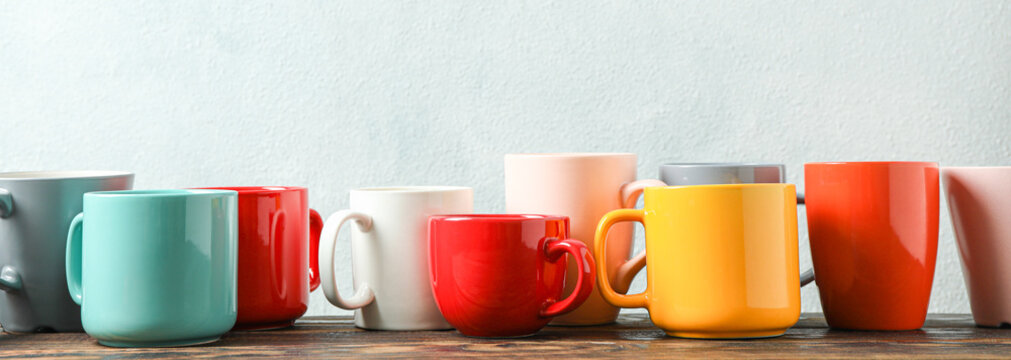 Multicolored cups on wooden table against light background, space for text