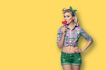 Photo of young woman eating heart shape lollipop, dressed in pinup style, over yellow