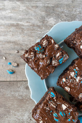 brownie squares with bright blue candy pieces and drizzled chocolate on top flat lay
