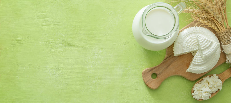 Shavuot concept - dairy products and wheat on green wood background, copy space