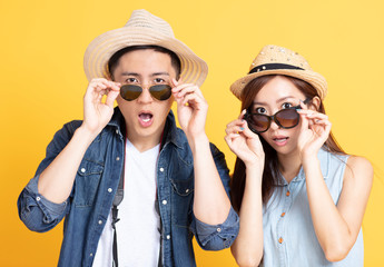 surprised Asian couple in summer casual clothes and sunglasses