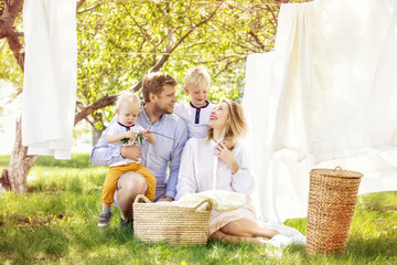 Family father, mother and two sons, beautiful and happy together hang clean Laundry in the garden